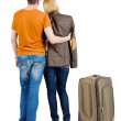 Back view of young couple traveling with suitcase . — Stockfoto #39359451