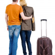 Back view of young couple traveling with suitcase . — Stockfoto #39359485