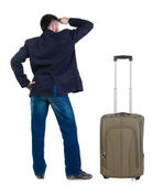 Young man traveling with suitcase looks ahead. Rear view. — Stock Photo