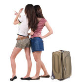 Two young women traveling with suitcase rear view. — Stock Photo