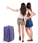 Two young women friends traveling with suitcase and showing thumbs up — Stock Photo