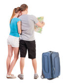 Young couple on a journey in search for the right route on map — Stock Photo