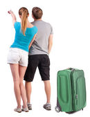 Young couple traveling with suitcas and pointing at wall — Stock Photo