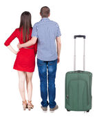Back view of young couple traveling with suitcase . — 图库照片