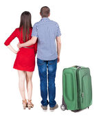 Back view of young couple traveling with suitcase . — Stock Photo
