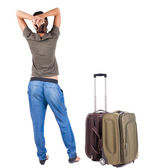 Back view of standing young beautiful brunette woman with suitcase — Stock Photo