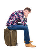 Back view of a man sitting on a suitcase. — Stock Photo