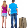 Back view of young couple traveling with suitcase. — Stockfoto #39360399