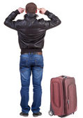 Back view of young man traveling with suitcase. — Stock Photo