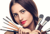 Beautiful woman with makeup brushes — Stockfoto