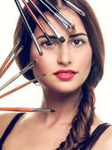 Beautiful woman with makeup brushes — Stok fotoğraf