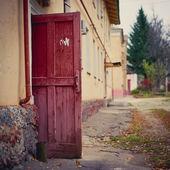 Open wooden door of a dilapidated building — Stock Photo