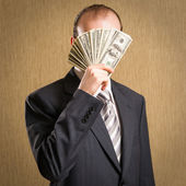 Man concealing his face with a fistful of money — Stock Photo
