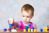 The child in a pink dress with toys — Stock Photo