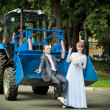 newlyweds on a tractor in park — Stock Photo