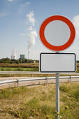 Red Road Sign and industrial building — Stock Photo