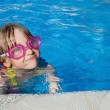 Little girl swimming in pool with goggles — Stock Photo