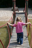 Little girl walking on a suspended wooden bridge — Stock Photo
