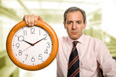 Mature handsome business man holding a clock — Foto de Stock