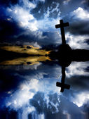 Cross silhouette at sunset with water reflection — Stock Photo