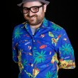 Young happy man with a hawaiian shirt on black background — Stock Photo
