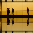 Workers inside the office building silhouette at sunset — Stock Photo