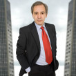 Mature business man standing with two office building behind — Stock Photo #23676383