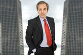 Mature business man standing with two office building behind — Stock Photo