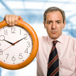 Mature handsome business man holding a clock — Stock Photo