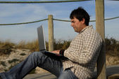 若い男が浜のコンピューターでの作業 — ストック写真