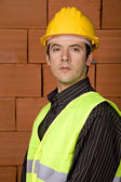 Engineer with yellow hat with a brick wall as background — Stock Photo