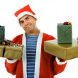 Young man with santa hat holding some gifts, isolated - Stock Photo