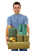 Young casual man holding a few gifts, isolated — Stock Photo