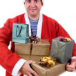 Young man with santa hat holding some gifts, isolated — Stock Photo