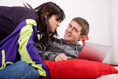 Young happy couple in bed with laptop — Stock Photo