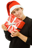 Young man with santa hat holding a gift — Stock Photo