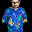 Young happy man with a hawaiian shirt on black background — Stock Photo #23767855