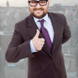 Young silly business man going thumb up — Stockfoto