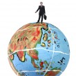Young business man in the top of a globe — Stock Photo #23787699