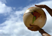 Globe in the woman hands and the sky — Stock Photo