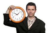 Young handsome business man holding a clock — Stockfoto