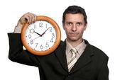 Hombre de negocios guapo joven sosteniendo un reloj — Foto de Stock