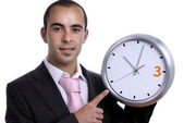 Handsome business man holding a clock — Stock Photo