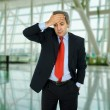 Businessman in a suit gestures with a headache — Lizenzfreies Foto