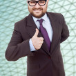 Stock Photo: Young silly business mgoing thumb up