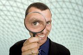 Business man with a loupe at the office — Stock Photo