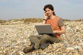 Casual ung med laptop på stranden — Stockfoto