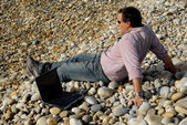 Young casual man with laptop at the beach — Stock Photo