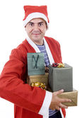 Young man with santa hat holding some gifts — Stock Photo