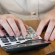 Masculine hands working on a calculator — Stock Photo #13862012